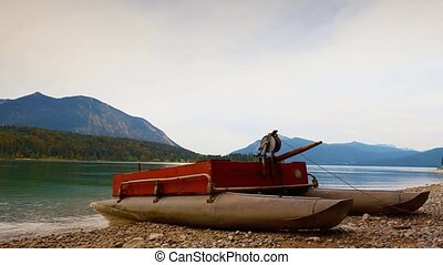 Time Lapse video. Raised view over small boat on gravel coast, mirror in water of mountain lake. Gentle waves on autumn water level, forest islands and high mountains in background.