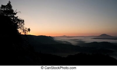 Last moments before autumn daybreak in hilly landscape. Hill...