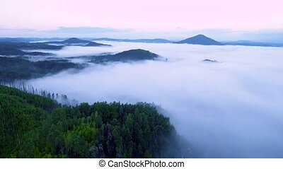 Time lapse. Hilly landscape in blue mist. Moving fog bellow...
