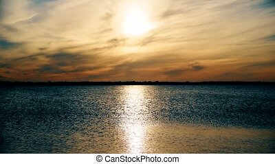 Sun shining on lake or river forming a sun way on water -...