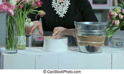 a florist make a bouquets box in white table with metal bucket