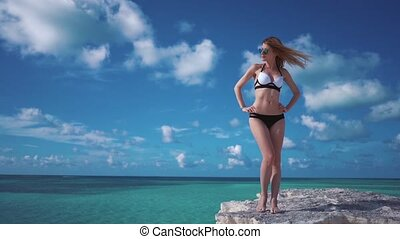 smiling girl Caribbean Sea. - A girl stands on a rock and...