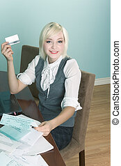 Young woman paying bills online using credit card - Friendly...