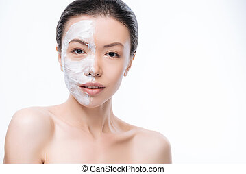 Young brunette woman having cream on her face