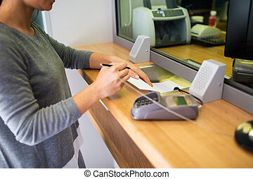 customer writing application at bank office