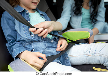 woman fastening child with safety seat belt in car - family,...