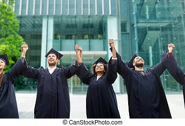happy students or bachelors celebrating graduation