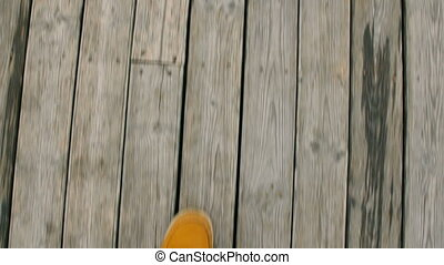 Walking on a pier at the beach, POV shot of a man with yellow shoes.