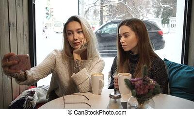 Girls make selfie in cafe.
