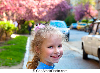 Happy small girl portrait and blossoming japanese cherry...