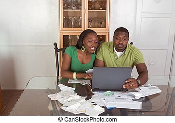 Young ethnic couple paying bills over internet - Financial...