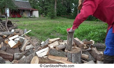 Strong village man prepare natural wood fuel for winter in...
