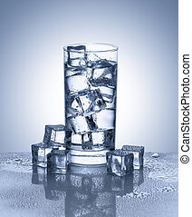 Glass of water with ice cubes on reflective surface