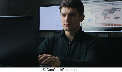 IT professional programmer is working on computer in cyber security center filled with display screens.