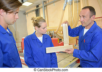 Carpenter demonstrating to two apprentices