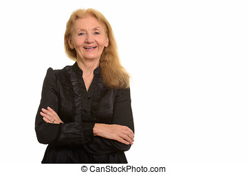 Studio shot of happy senior businesswoman smiling with arms...