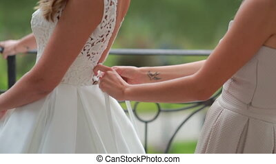 friend Help the bride to wear a wedding dress close up