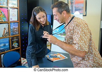 Man showing travel agent his holiday snaps