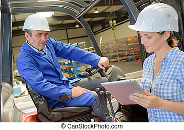 Woman using tablet next to man on forklift