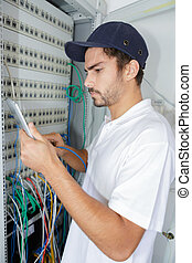 focused electrician applying safety procedure while working on electrical panel
