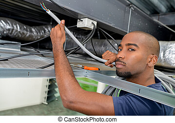 Man doing wiring in roof space