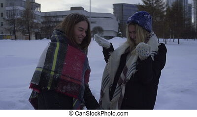 Two girls having fun and playing with snow outdoors in winter