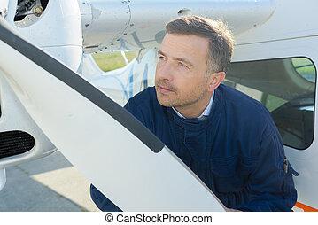 Mechanic looking at aircraft propellor