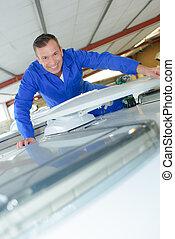 Portrait of mechanic on roof of camper van