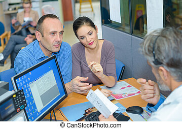 Couple at desk in waiting room