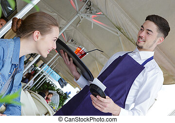 young woman in coffee flirting with male waiter