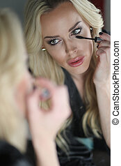 Beautiful Blond Woman with Green Eyes Applying Mascara -...