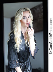 Beautiful Blond Woman with Green Eyes Applying Lipstick -...