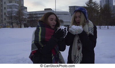 Two girls having fun and playing with snow outdoors in...