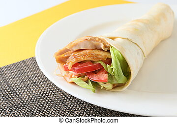 The kebab wrap roll with tomatoes and lettuce on white...