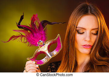 Beautiful girl holds carnival mysterious mask.
