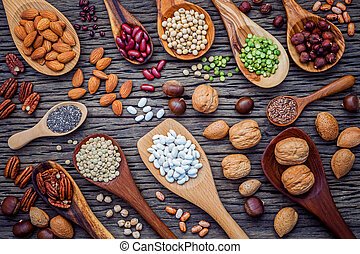 Various legumes and different kinds of nutshells in spoons....