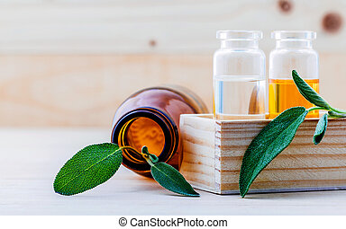 Closeup bottles of sage essential oil for aromatherapy with...