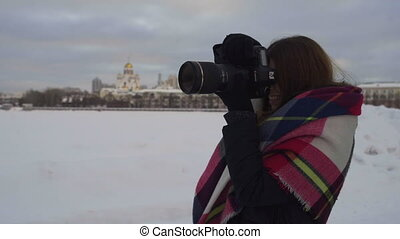 The girl photographing in the winter on the street.