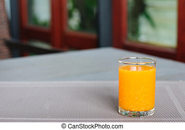 Small single glass of orange juice on napery