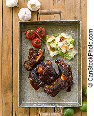 Slow roasted Beef Short Rib Barbecue with Sauce, garlic, tomatoes on iron platter