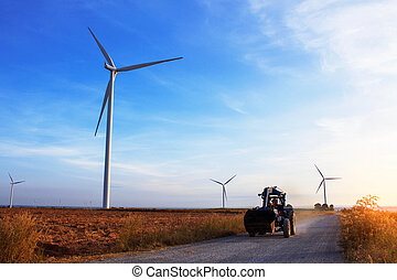 tractors on a rural road with a wind farm.