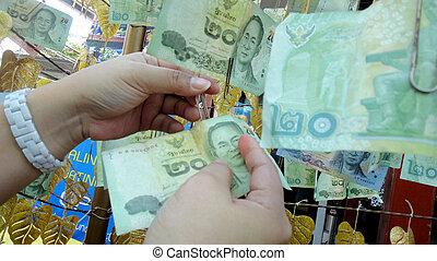 merit - Buddhists make merit,Stick cash the rope around the...