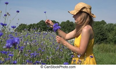 Cute girl in yellow dress pick blue flowers bouquet. Focus...