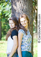 Sisters leaning against a tree