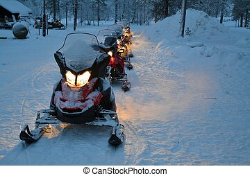 snowmobiles in line - A line of snowmobiles with their...