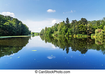 Summer rural landscape. Trees and sky reflected on the...
