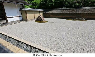 Zen Rock Garden in Ryoan-ji Temple, Kyoto, Japan. The stones...