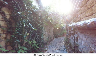 Narrow lane with sun in frame - Down narrow lane mountain...