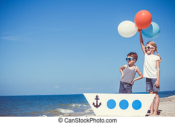 Happy children playing on the beach at the day time. Concept...