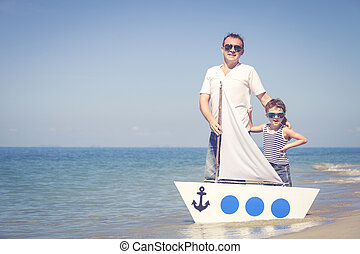 Father and son playing on the beach at the day time. Concept...